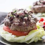 Bun-less lamb burger with lettuce, tomato, Greek olives, feta cheese and mint on a plate.