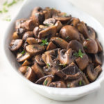 Quartered sauteed mushrooms in white wine sauce with thyme in a white dish.