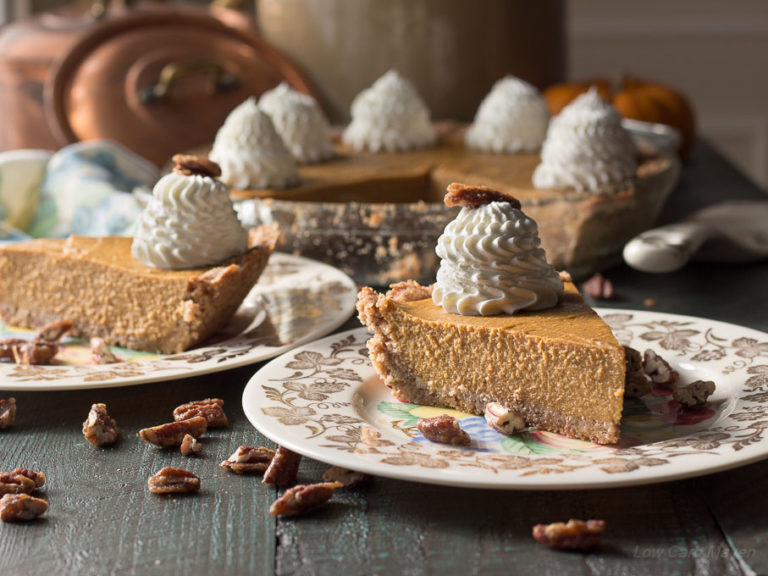 Two slices of sugar-free pumpkin pie with whipped cream on china plates with the remaining pumpkin pie in a pie plate behind. Pecans are scattered on the wooden surface in the foreground.