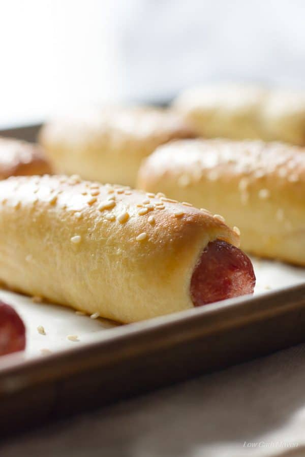 Baked low carb bagel dogs or pretzel dogs with sesame seeds on a cookie sheet.