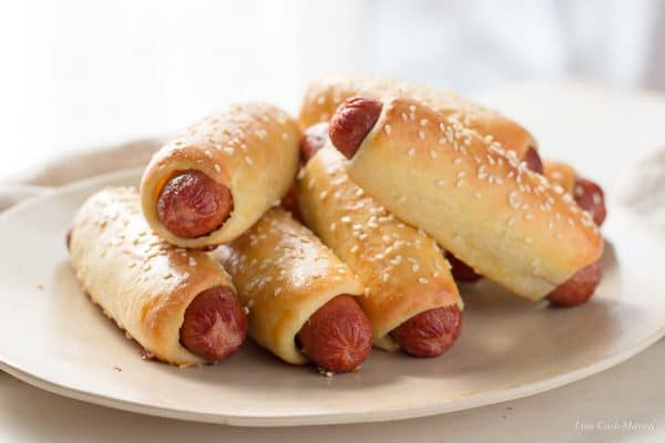 Bagel dogs or pretzel dogs wrapped in fathead pizza crust dough with sesame seeds stacked on an oval platter.