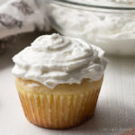 A sugar free cupcake slathered in whipped cream cheese frosting with a bowl of frosting behind.