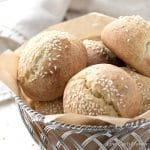 Round low carb rolls with sesame seeds and split tops in a woven aluminum basket lined with a brown piece of parchment and a beige napkin in the background.