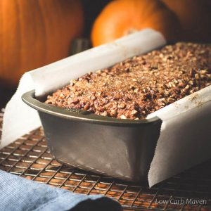 Pumpkin bread made with coconut flour in a pan with pumpkins and blue napkin.