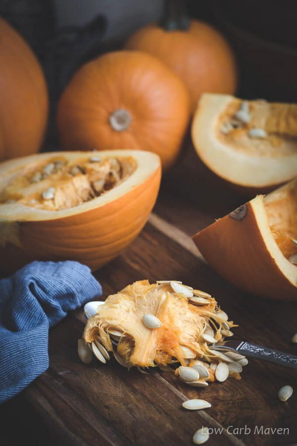 Cut and whole pumpkins on a cutting board with a blue napkin and freshly scooped pumpkin seeds.