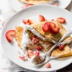 Folded Keto strawberry crepes and whipped cream on a plate with napkin.