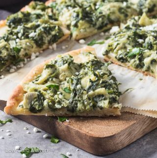 Slices of spinach artichoke pizza on cutting board.