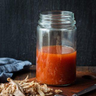 Carolina BBQ Sauce (apple cider vinegar sauce) in a jar with pulled pork.