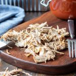 Easy Pulled Pork Recipe is easily shredded with forks on a cutting board.