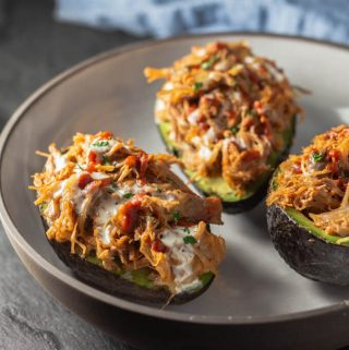Stuffed avocados or avocado boats with pulled pork, cheese, and BBQ sauce in a bowl.