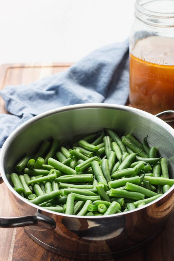 Cut green beans in a pot with ham stock in a jar.