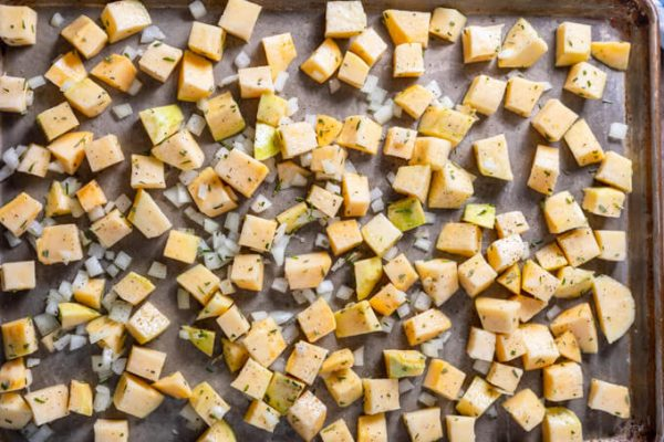 Cubed rutabaga and onions on a sheet pan.