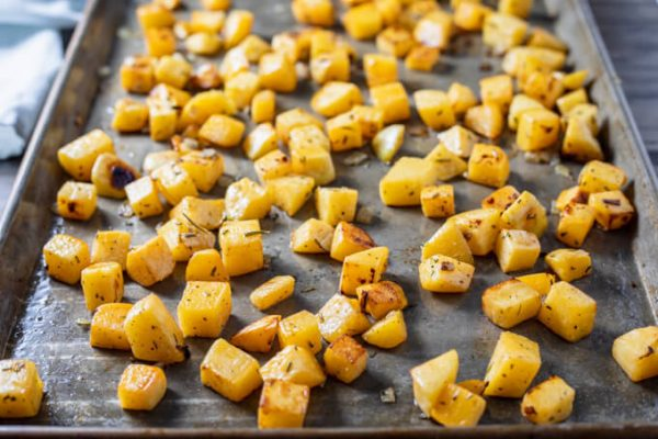 Roasted rutabaga cubes and onion on a sheet pan.