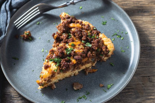 A slice of sloppy Joe Casserole on plate with fork.