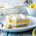 Lemon lush layered dessert on a plate with fork.