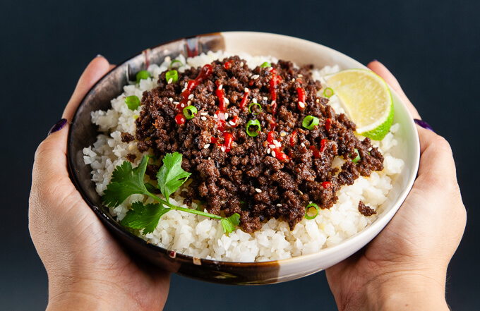 Hands holding a bowl of Korean ground beef with Siracha and lime over cauliflower rice.