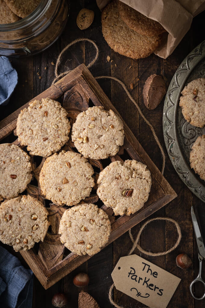 Pecan sandies cookies on a trivet with more on a platter with nuts and twine around