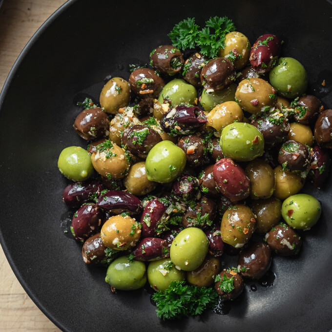 Green and black marinated olives with herbs, spices, garlic, oil and vinegar with parsley in a black bowl
