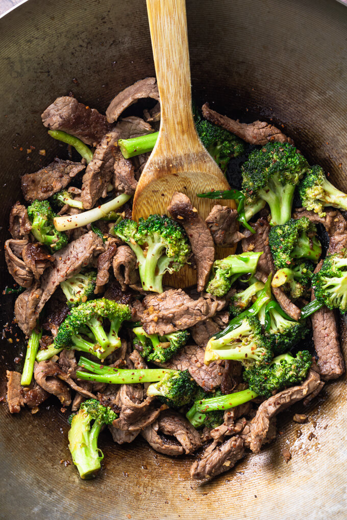 Keto beef and broccoli stir fry in a wok with bamboo spoon