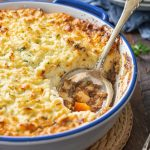Baked keto shepherd's pie with mashed cauliflower topping in blue rimmed casserole dish with spoon.