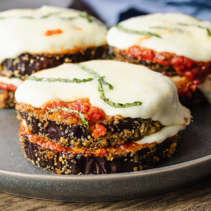 Stacks of keto eggplant parmesan rounds with marinara sauce and melted mozzarella cheese topped with basil